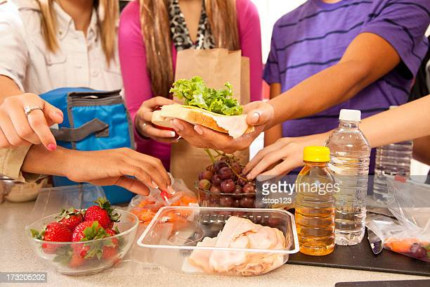 Multi-ethnic group teenagers in kitchen making school lunches.