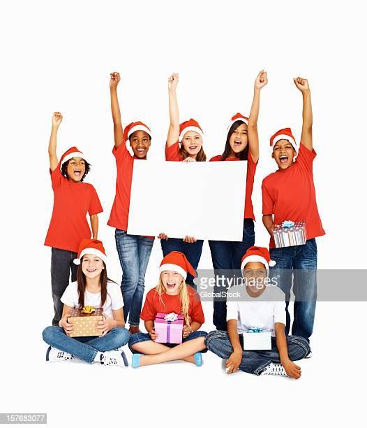 Multi ethnique enfants portant des chapeaux avec vos mains posées tenant une planche à repasser