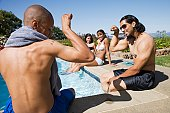 Multi-ethnic men flexing at swimming pool