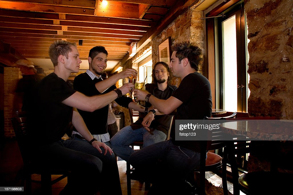 Multi-ethnic men friends at the bar sharing beer, drinks. Cheers!