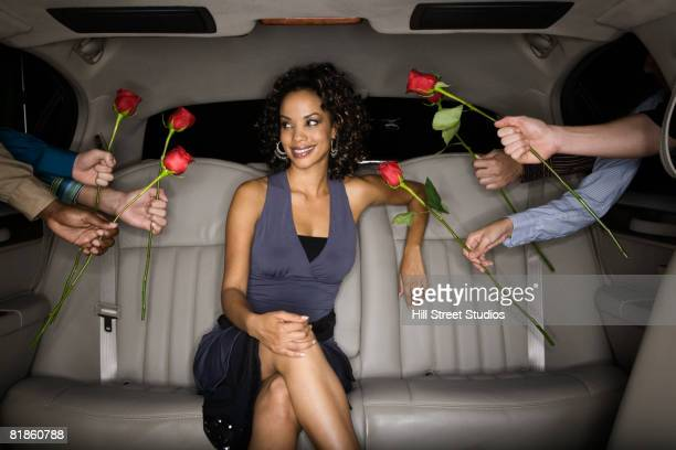 Multi-ethnic men handing roses to African woman in limousine