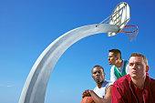 Multi-ethnic men under basketball hoop