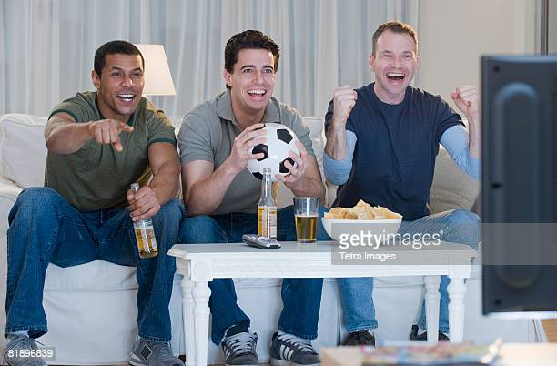 Multi-ethnic men watching sports on television