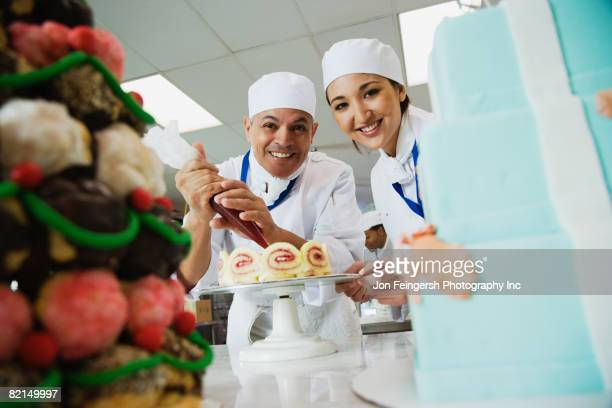 Multi-ethnic pastry chefs decorating cake