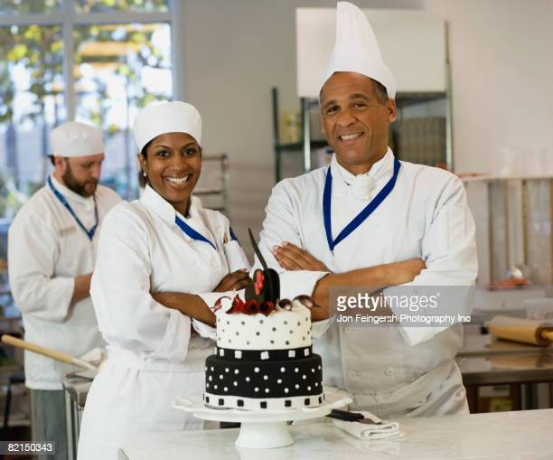 Multi-ethnic pastry chefs next to cake