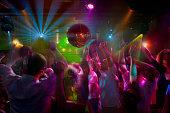 Multi-ethnic people dancing at night club