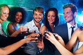 Multi-ethnic people toasting shots
