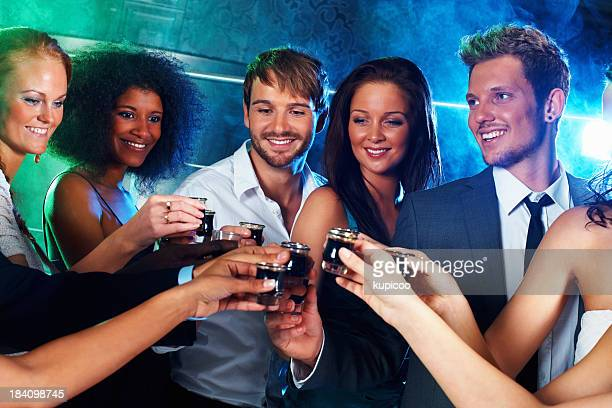 Multi-ethnic people toasting shots
