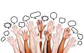 Multiethnic people's hands raised with speech bubble