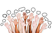 Multiethnic people's hands raised with speech bubble