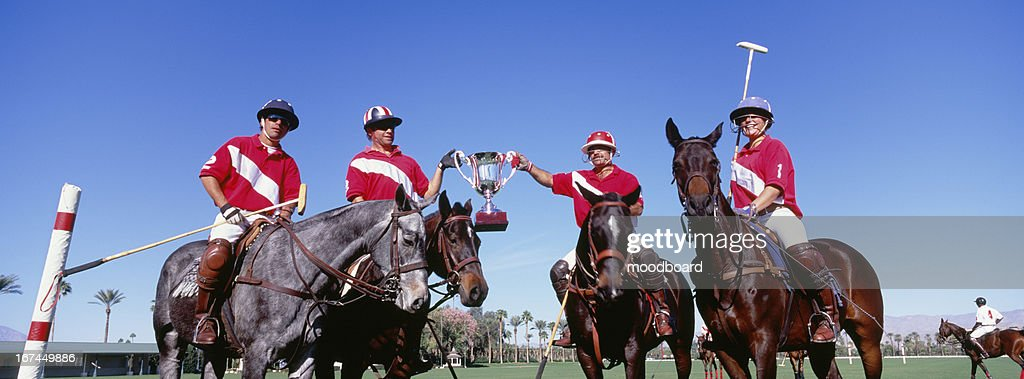 Multiethnic polo team celebrating with trophy on field : Stock Photo