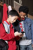 Multi-ethnic school boys looking at cell phone