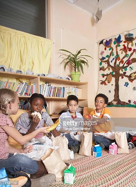 Multi-ethnic school children eating lunch