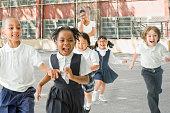 Multi-ethnic school children running from teacher outdoors