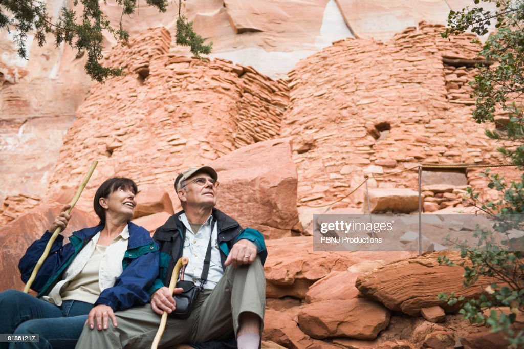 Multi-ethnic senior couple holding walking sticks