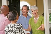 Multi-ethnic senior couples greeting in doorway
