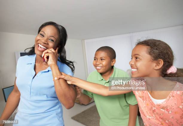 Multi-ethnic siblings pulling on mother's hand with cell phone