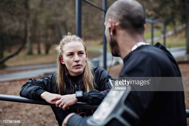 Multi-ethnic sporty couple talking while leaning on parallel bars in forest