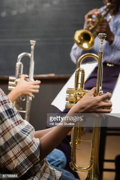 Multi-ethnic students holding trumpets in classroom