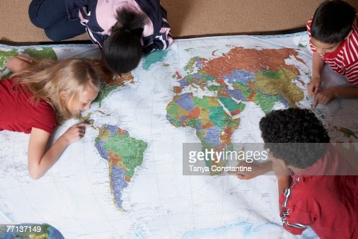 Multi-ethnic students looking at world map