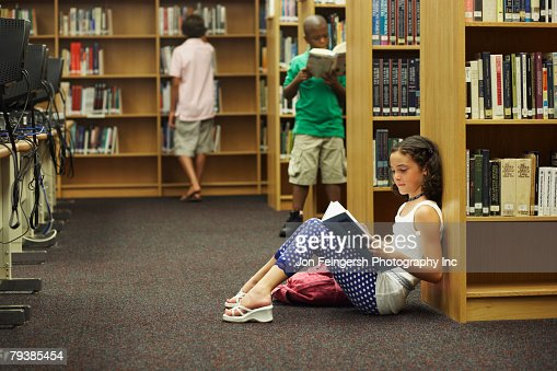 Multi-ethnic students reading library books : Stock Photo