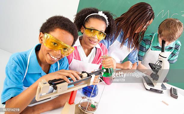 Multi-Ethnic students science lab safety glasses microscope and scale