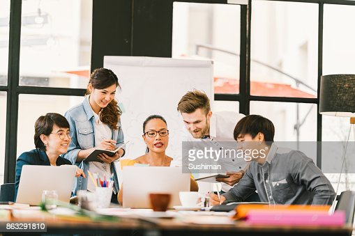 Multiethnic team busy discussion using laptop, digital tablet. Coworker partnership, college student meeting. Small business casual office, freelance designer job, or online marketing analysis concept : Stock Photo