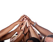 Large Group of people raising and joining their hands up high to celebrate their teamwork or success.