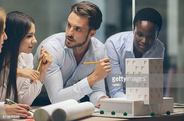 Multiétnica equipo de arquitectos Revisar modelo arquitectónico en la oficina.