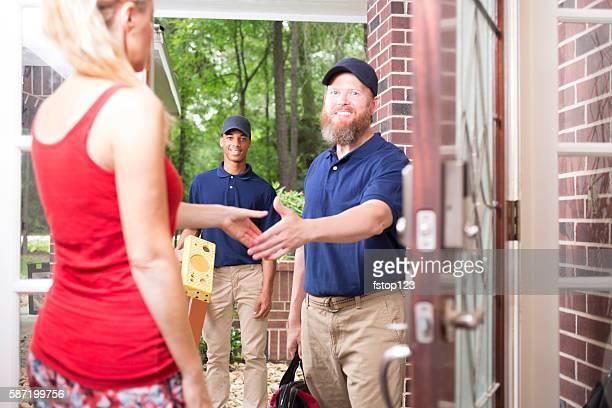 Multi-ethnic team of repairmen at customer's front door.