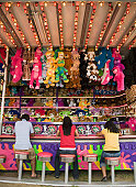 Multi-ethnic teenaged friends playing carnival game