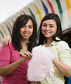 Multi-ethnic teenaged girls eating cotton candy