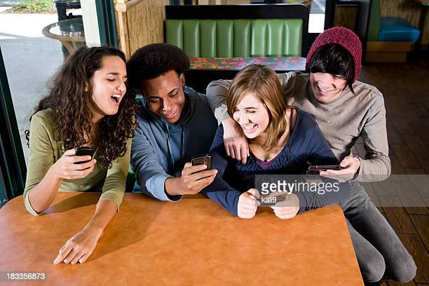 Multi-ethnic teenagers in diner texting on mobile phones