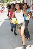 Multi-ethnic teenagers running on sidewalk