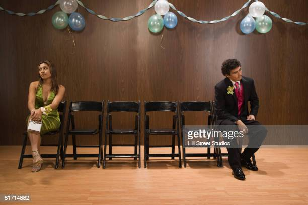 Multi-ethnic teenagers sitting apart at prom