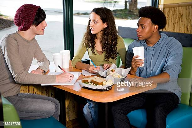 Multi-ethnic teenagers studying in restaurant over lunch