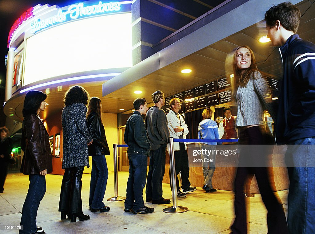 Multi-ethnic teens (14-18) lining up to buy movie tickets