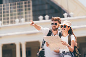 Multiethnic traveler couple using generic local map together on sunny day, man pointing toward copy space. Honeymoon trip, backpacker tourist, Asia tourism, or holiday vacation travel concept