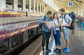 Multiethnic Travellers are looking at train and holding the map with happiness action at the train station, Travel and transportation concept