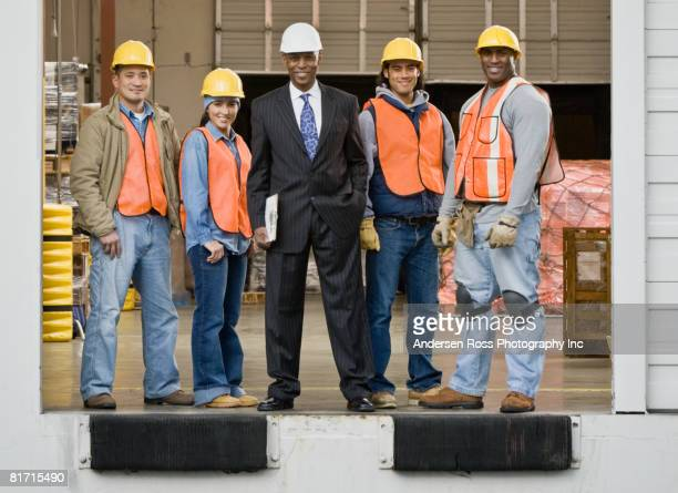 Multi-ethnic warehouse workers and businessman on loading dock
