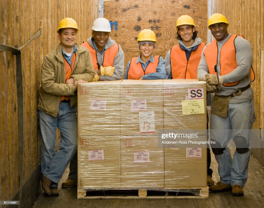 Multi-ethnic warehouse workers next to shipment : Stock Photo