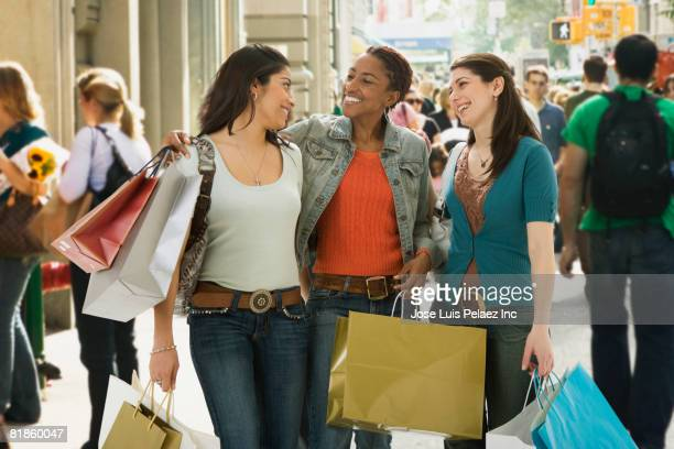 Multi-ethnic women carrying shopping bags