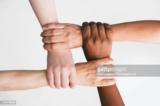 Multi-ethnic women holding wrists