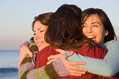 Multi-ethnic women hugging at beach