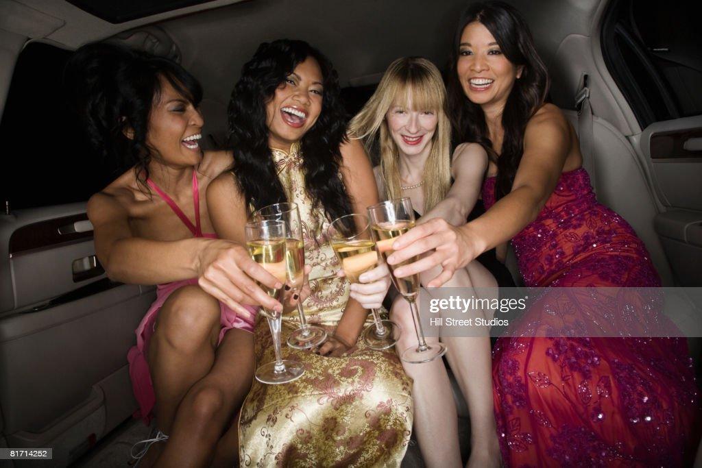 Multi-ethnic women toasting in limousine : Stock Photo