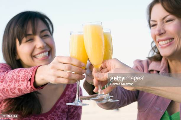 Multi-ethnic women toasting with mimosas