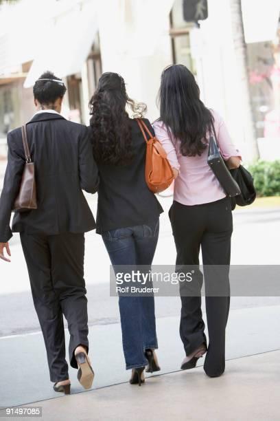 Multi-ethnic women walking on sidewalk