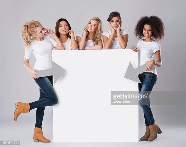 Multi-ethnic women with empty billboard. Debica, Poland