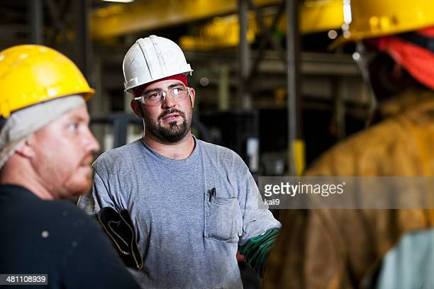 Multi-ethnic workers in fabrication shop talking