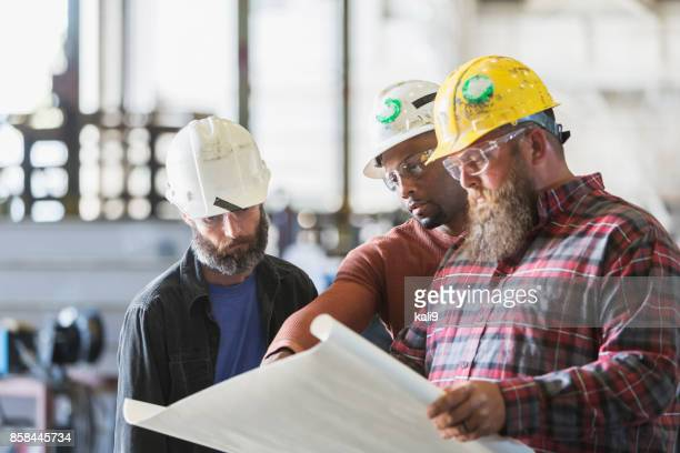 Multi-ethnic workers in hardhats examining plans